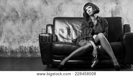 Beautiful Woman With A Revolver In Her Hands Sits On The Couch
