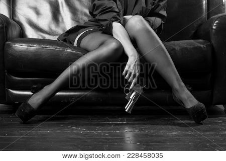 Beautiful Female Legs In Shoes And A Revolver In Her Hands