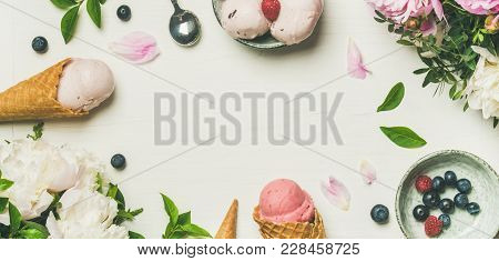 Flat-lay Of Pink Strawberry And Coconut Ice Cream Scoops, Sweet Cones And Peony Flowers Bouquet Over