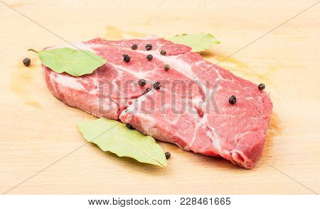 Raw Pork Neck Meat Cut On Wood Background Fresh One Slice Without Bone With Black Pepper And Bay Lea