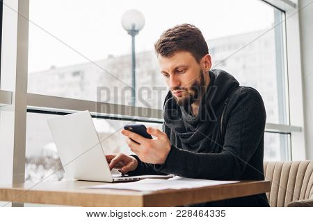 Bearded Hipster Working At A Laptop In A Cafe, Young Man Sitting At The Cafe And Using Laptop