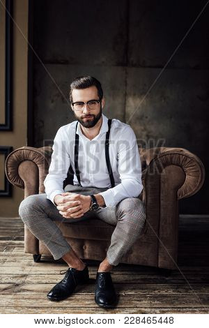 Fashionable Man In Glasses And Suspenders Sitting In Armchair