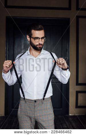 Fashionable Elegant Man Posing In White Shirt And Suspenders Against Door In Loft Interior