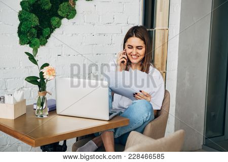Young Freelancer Girl Talking On The Phone, Holding A Notebook, Laptop On The Table, Beautiful Young