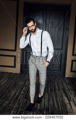 Fashionable Elegant Man Posing In White Shirt And Suspenders In Loft Interior