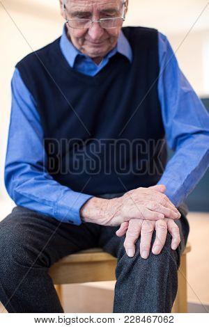 Senior Man Suffering With Parkinsons Diesease Holding Hand