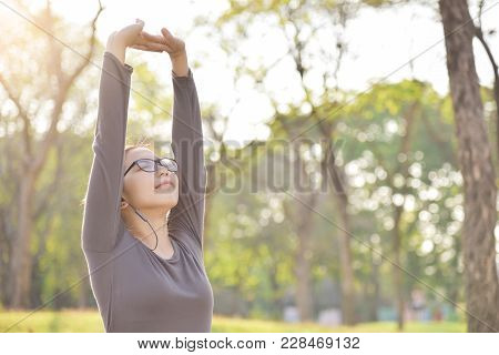 Happy Asian Female In Grey Sportswear Workout At The Park. Young Woman Is Warming Up And Stretching