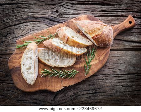 Slices of ciabatta with rosemary herb on the wooden tray. Top view.