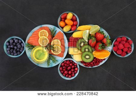 Healthy nutrition for good health concept with super foods of fresh salmon fish, fruit, vegetables, herbs and olive oil very high in antioxidants, anthocyanins, vitamins, minerals and fibre on slate.