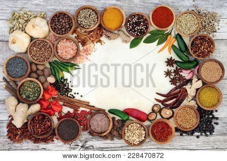 Spice and herb border with fresh and dried herbs and spices on parchment paper and rustic wood  background. Top view.