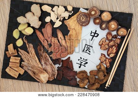 Chinese alternative medicine with herb selection and calligraphy script on rice paper. Translation reads as chinese alternative medicine.