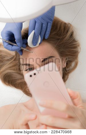 Blackhead cleansing on woman face during facial treatment at beauty clinic, while woman makes selfie on her mobile