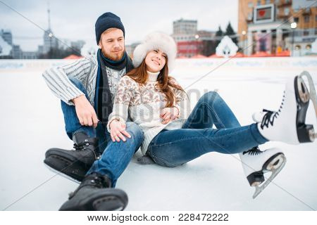 Love couple in skates sitting on ice, skating rink