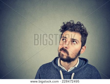 Young Bearded Man In Puzzlement Looking Up And Considering Problem In Mindfulness.