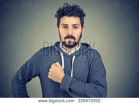 Optimistic Young Hipster Looking Brave And Motivated Holding Hand On Chest And Looking At Camera.