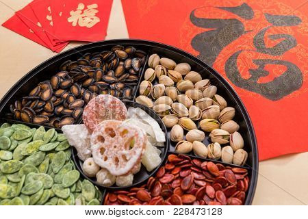 Lunar new year chinese snack tray with red packet and Chinese calligraphy word means luck