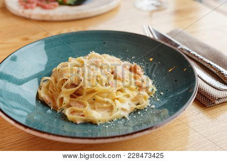 Pasta carbonara cooked with cream and grated cheese in clay plate