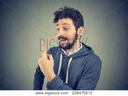 Man With Long Nose Isolated On Gray Wall Background. Liar Concept. Human Emotions, Feelings.