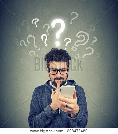 Young Man Having Questions While Using Contemporary Device In Puzzlement.
