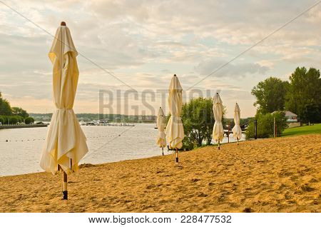 Umbrellas On The Beach Next To Pond At Sunset