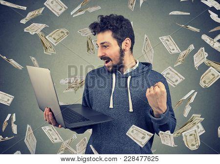 Successful Young Man Using Laptop Building Online Business Making Money Dollar Bills Cash Falling Do