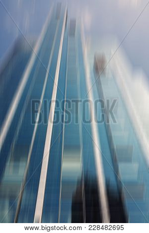Low Angle Exterior Of Blurred Modern Skyscraper In The Commercial District Of A City Rising Up Again