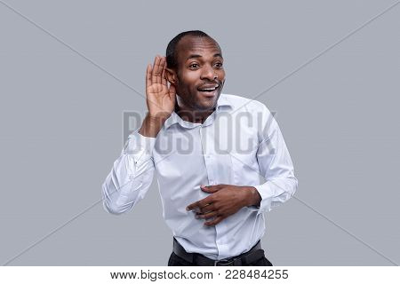 Say More Loudly. Attractive Happy Dark-eyed Afro-american Man Smiling And Having His Hand Hear His E