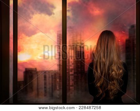 The Girl Looks Through The Window At The Burning City. Concept - War, Natural Disasters, The Death O