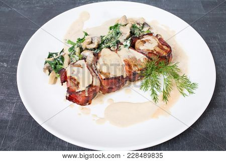 Bacon Wrapped Pork Tenderloin With Spinach And Mushrooms. Plate Located On A Black Table As A Backgr