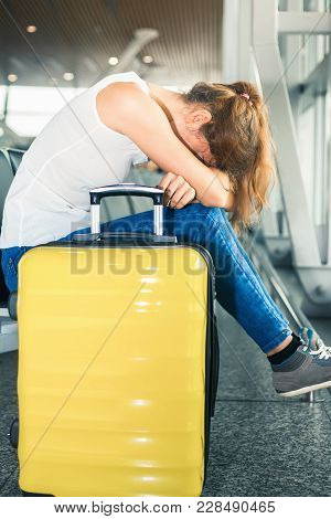 Woman Sitting At The Airport Near Her Luggage In Terminal Of Hong Kong. Some Problem Concept