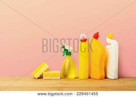 Group Of Yellow Bottles, Cleaning Products And Sponges On Pink Background. House Keeping, Tidying Up