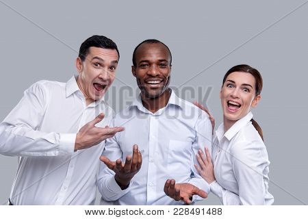 Having Fun. Exuberant Young Dark Haired Co-workers Smiling And Wearing White Shirts And Having Fun