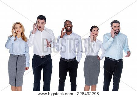 Work Calls. Good-looking Young Successful Colleagues Standing In One Line And Talking On Their Phone