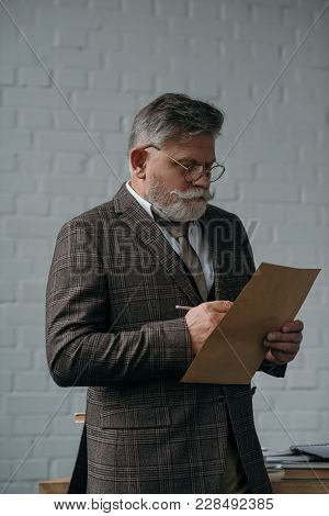 Senior Man In Tweed Suit Writing Letter In Front Of White Brick Wall