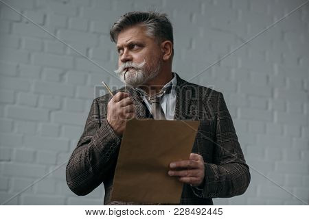 Thoughtful Senior Man With Pencil And Sheet Of Paper Looking Away