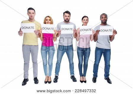 Charity. Attractive Inspired Kind-hearted Young Men And Women Wearing Casual Clothes And Smiling And