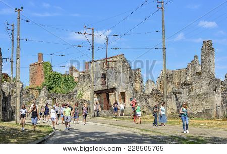 Oradour Sur Glane, France - August 16, 2017: The Tourists Looks At The Ruined Building During World