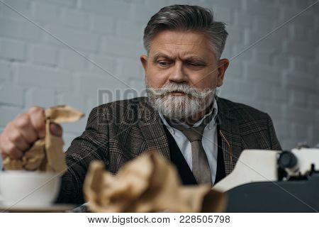 Depressed Senior Writer Crumpling Paper At Workplace