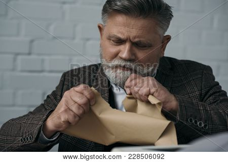 Close-up Portrait Of Disappointed Senior Writer Tearing His Manuscript