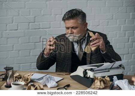 View Of Depressed Senior Writer Tearning His Manuscript