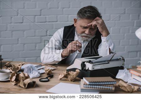 Depressed Senior Writer Trying To Work At Messy Workplace