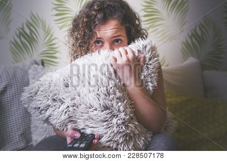 Scared young woman watching horror movie on TV