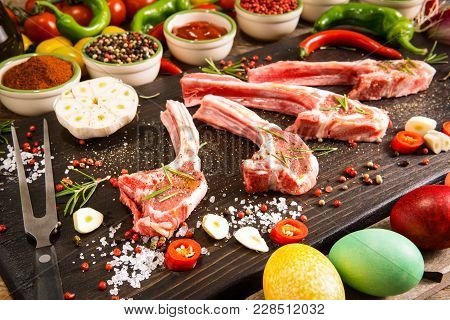 Raw Lamb Ribs Preparation On Rustic Cutting Board - Fresh Chops Of Meat With Colorful Spices And Veg