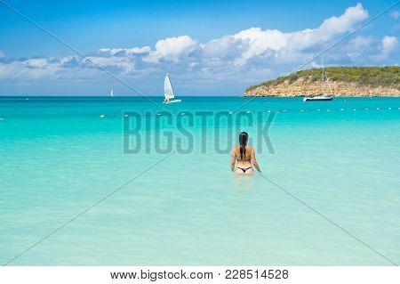Sensual Girl In Sexy Bikini On Sea Beach In Antigua. Woman In Blue Sea Or Ocean Water On Sunny Day.