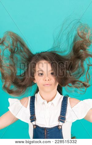 Child With Long Healthy Hair. Girl With Flying Hair On Blue Background. Beauty Salon Concept. Hairca