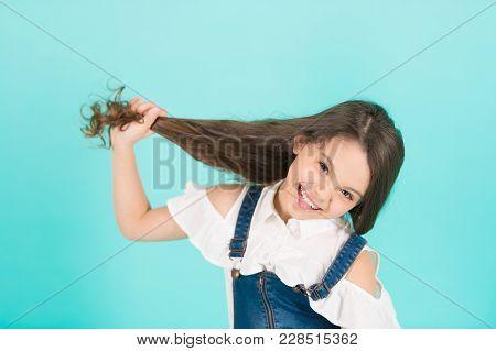 Beauty Or Hairdressing Salon. Girl Hold Long Hair On Blue Background. Child Smile With Healthy Brune