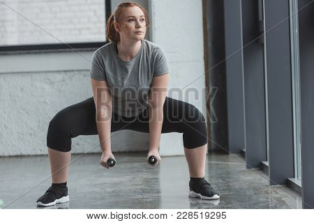 view of Curvy girl lifting dumbbells in gym poster