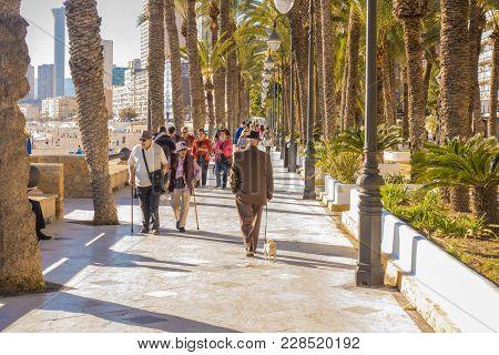 Benidorm, Spain, February 14, 2018: Eldery People Walking On The Embankment Street In Benidorm, Spai
