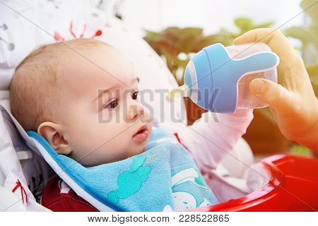 Adorable Curious Baby Drinks Water From The Bottle. Happy And Emotional.