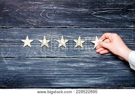 A Woman's Hand Puts The Fifth Star. Quality Status Is Five Stars. A New Star, Achievement, Universal